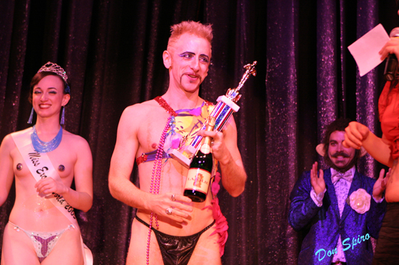 This shot is of Tigger!, winner of the men's competition in 2006, the first year of the award in that category. The look on his face shows the significance of the moment, one that changed the manner of the Pageant and one that helped to validate the then somewhat controversial idea of men performing burlesque. On stage with him are Miss Exotic World 2005 Michelle L'amour and future winner Monkey.  ©Don Spiro